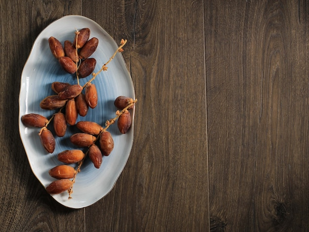 Vue de dessus dattes séchées fruits ob plaque ovale au-dessus d'une table en bois marron, espace de copie pour le texte ou le dépliant promotionnel (publicité)