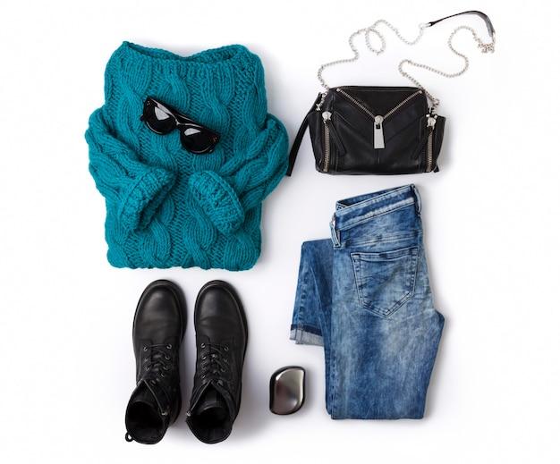 Vue de dessus décontractée à plat style féminin avec un pull turquoise chaud, des bottes, un jean, un sac à main et des lunettes de soleil.