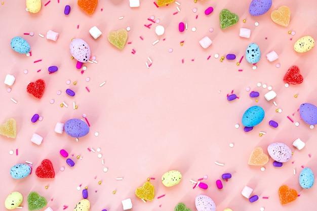 Vue de dessus de la décoration de l'arrangement concept de fond de joyeuses fêtes de pâques. oeufs de lapin colorés à plat sur un beau bureau rose. espace de copie.