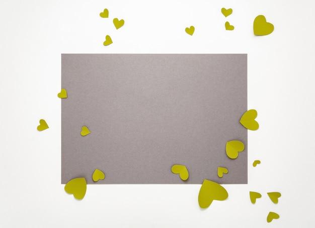 Vue de dessus des décorations de la saint-valentin à plat. coeurs jaunes verts sur fond gris. bannière de la saint-valentin heureuse