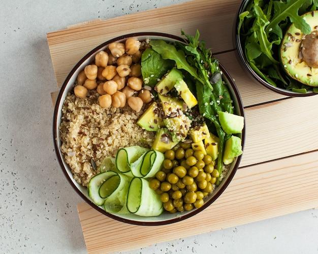 Vue de dessus déjeuner de légumes sains avec quinoa, avocat, pois chiches et concombre
