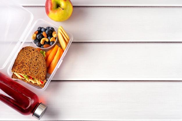 Vue de dessus d'un déjeuner scolaire sain dans une boîte, pomme et bouteille de jus rouge