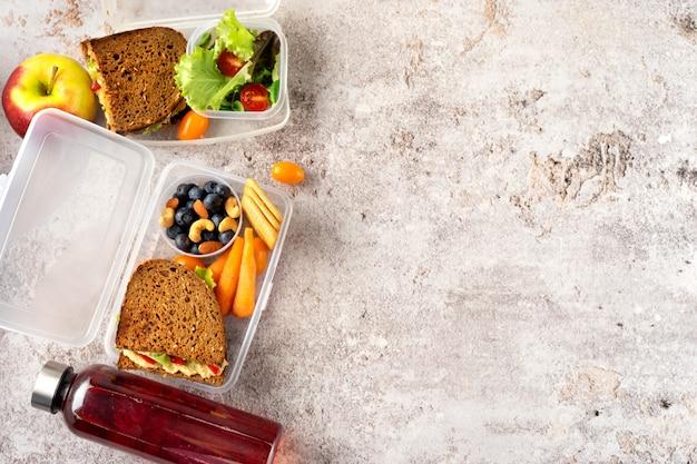 Vue de dessus des déjeuners scolaires végétaliens avec des sandwichs sains, de la salade et des fruits