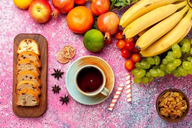 Vue de dessus délicieuse composition de fruits avec des gâteaux en tranches sur le bureau rose