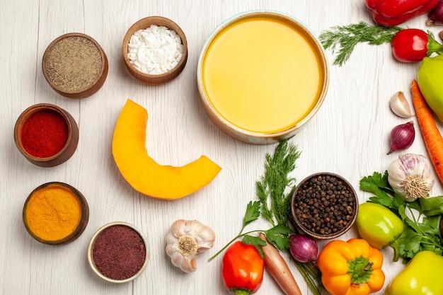 Vue de dessus délicieuse crème de soupe à la citrouille texturée avec des légumes sur un bureau blanc repas de sauce à soupe mûre