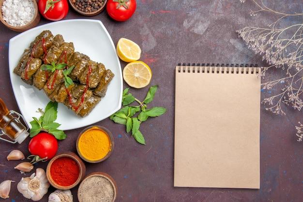 Vue de dessus délicieuse feuille dolma avec assaisonnements et tomates sur fond sombre plat feuille nourriture viande dîner