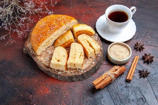 Vue de dessus délicieuse pâtisserie sucrée avec tasse de thé sur une surface sombre