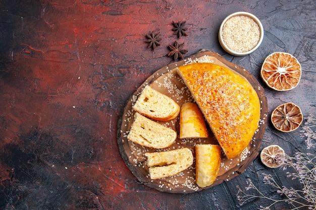 Vue de dessus délicieuse pâtisserie sucrée tranchée en morceaux sur une surface sombre