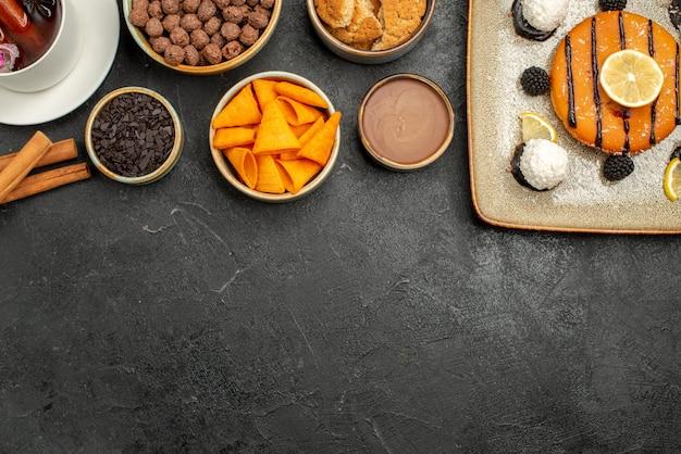 Vue de dessus délicieuse petite tarte avec une tasse de thé sur une surface sombre biscuit bonbons biscuit gâteau tarte sucré