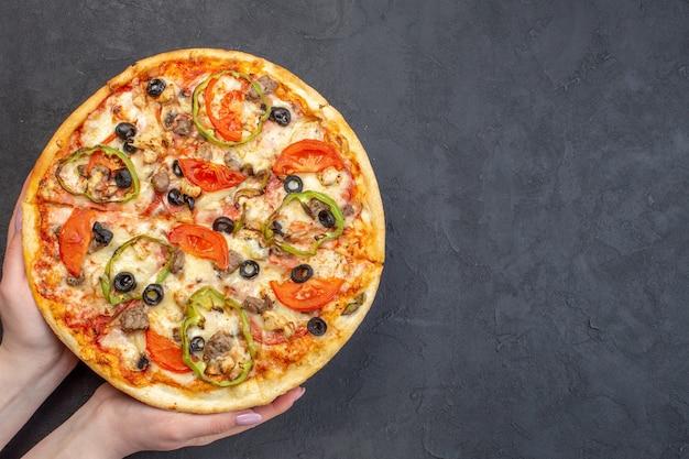 Vue de dessus délicieuse pizza au fromage aux olives, poivrons et tomates sur une surface sombre