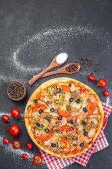 Vue de dessus délicieuse pizza au fromage avec des tomates rouges sur une surface sombre