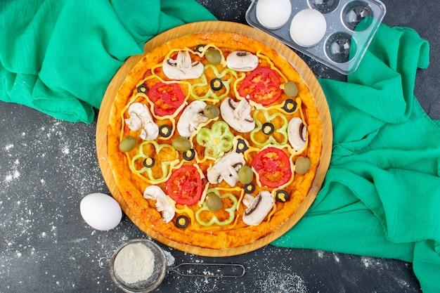 Vue de dessus délicieuse pizza aux champignons avec tomates olives champignons tous tranchés à l'intérieur avec de la farine sur le bureau sombre pâte à pizza tissu vert cuisine italienne