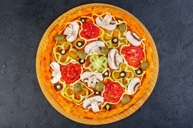 Vue de dessus délicieuse pizza aux champignons avec tomates poivrons, olives et champignons tous tranchés à l'intérieur sur le bureau sombre repas alimentaire pizza italienne