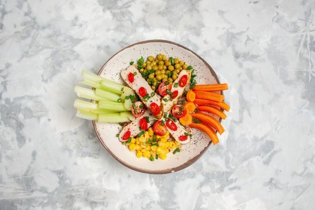 Vue de dessus de la délicieuse salade sur une assiette sur une surface blanche tachée
