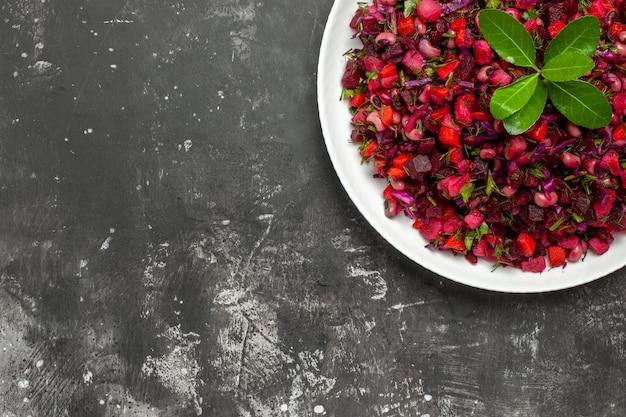 Vue de dessus délicieuse salade de betteraves vinaigrette avec des haricots sur la surface sombre