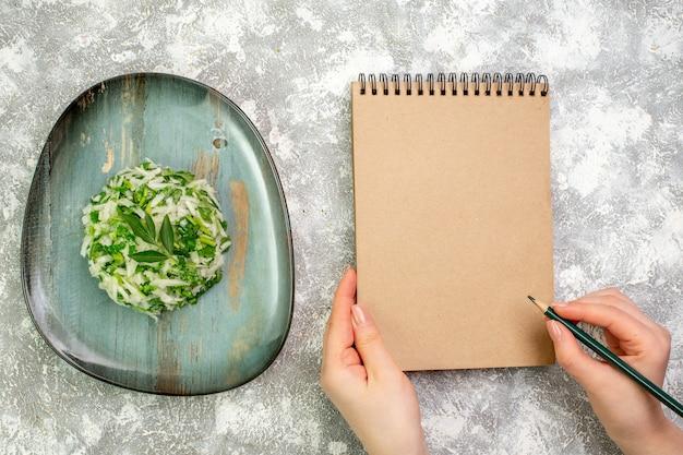 Vue de dessus une délicieuse salade composée de légumes verts et de chou à l'intérieur d'une assiette