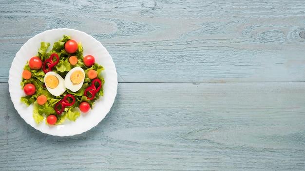 Une vue de dessus d'une délicieuse salade dans une assiette blanche