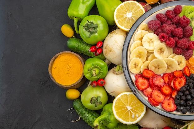 Vue de dessus une délicieuse salade de fruits à l'intérieur de la plaque avec des fruits frais sur l'arbre fruitier tropical gris photo de régime mûr exotique