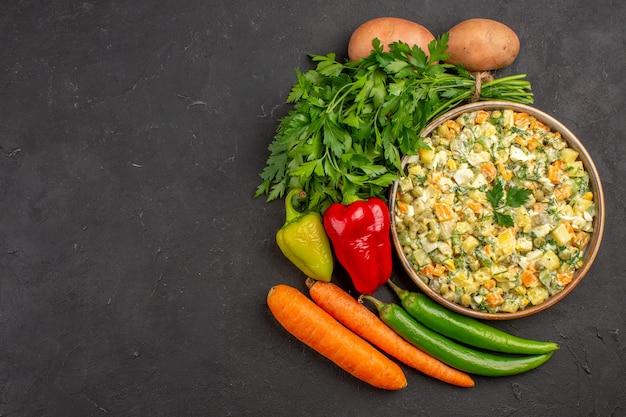 Vue de dessus de la délicieuse salade avec des légumes frais sur une surface sombre
