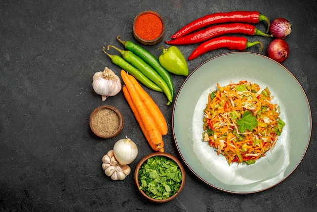 Vue de dessus une délicieuse salade avec des légumes frais sur une table sombre régime alimentaire salade santé