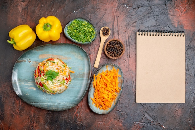 Vue de dessus une délicieuse salade de légumes avec des légumes verts et des carottes sur fond sombre couleur repas mûrs repas vie saine photo