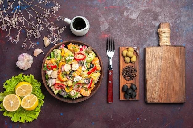 Vue de dessus délicieuse salade de légumes avec tranches de citron et salade verte sur fond sombre repas régime salade santé