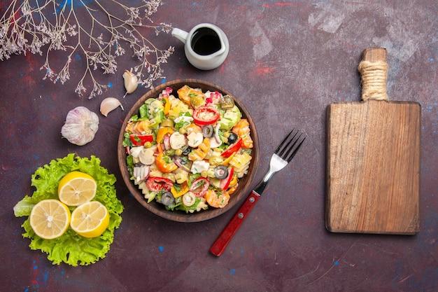 Vue de dessus délicieuse salade de légumes avec tranches de citron et salade verte sur fond sombre repas santé régime salade