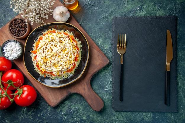 Vue de dessus délicieuse salade de mimosa à l'intérieur de la plaque avec des tomates rouges sur fond bleu foncé