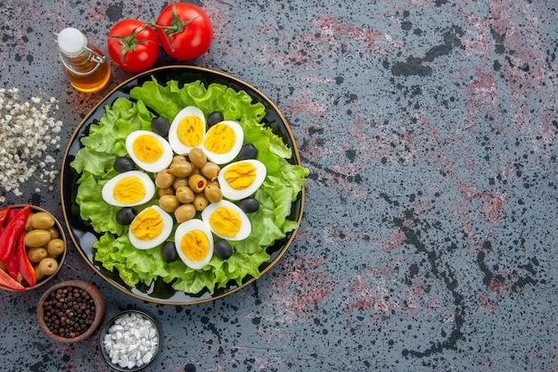 Vue de dessus délicieuse salade d'oeufs aux tomates et olives sur fond clair