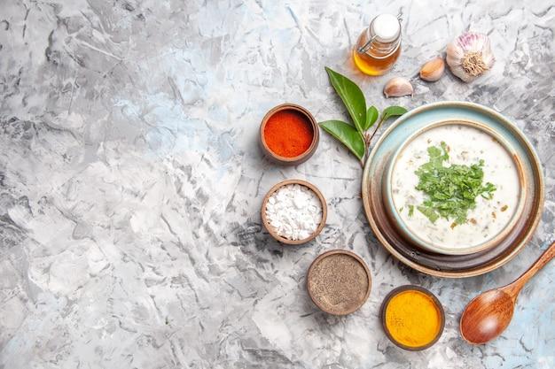 Vue de dessus délicieuse soupe au yaourt dovga avec assaisonnements sur un plat blanc lait de soupe lait