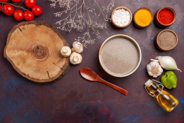 Vue de dessus délicieuse soupe aux champignons avec des assaisonnements sur un espace sombre