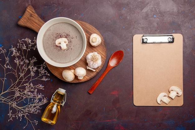 Vue de dessus délicieuse soupe aux champignons avec des champignons frais et de l'huile sur un bureau sombre