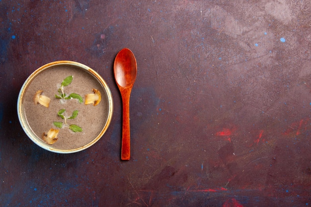 Vue de dessus délicieuse soupe aux champignons à l'intérieur de la plaque sur un bureau sombre