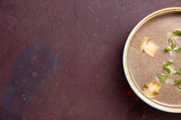 Vue de dessus délicieuse soupe aux champignons à l'intérieur de la plaque sur l'espace sombre