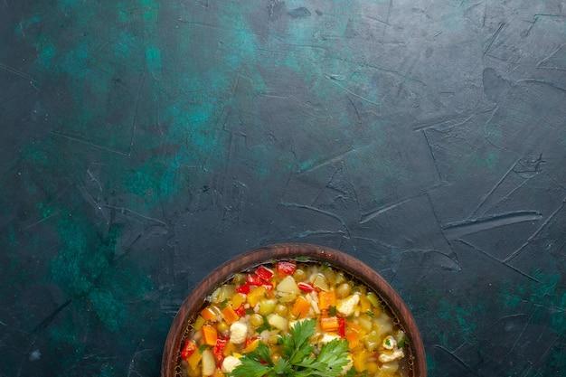 Vue de dessus délicieuse soupe aux légumes avec différents ingrédients à l'intérieur du pot brun sur le bureau sombre soupe légumes sauce repas nourriture chaude