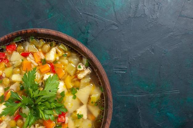 Vue de dessus délicieuse soupe aux légumes avec différents ingrédients à l'intérieur du pot brun sur le bureau sombre soupe sauce aux légumes repas nourriture chaude