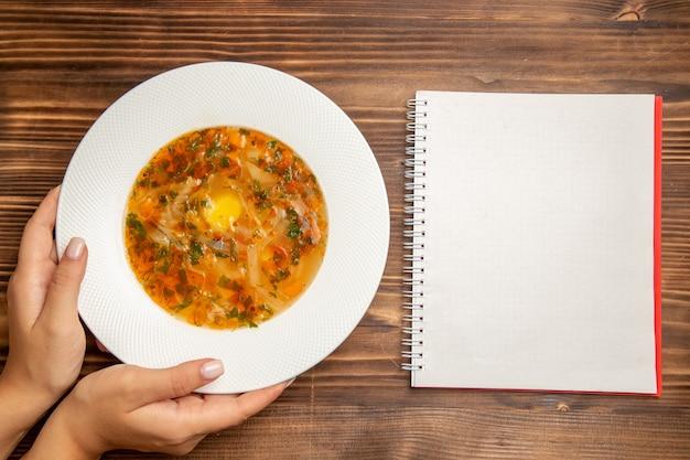 Vue de dessus délicieuse soupe aux légumes avec des verts et bloc-notes sur table en bois brun soupe assaisonnements de légumes
