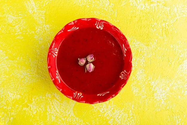 Vue de dessus délicieuse soupe aux tomates à l'intérieur de la plaque rouge sur la table jaune, soupe repas dîner nourriture végétale