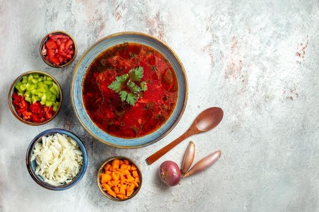 Vue de dessus délicieuse soupe de betterave ukrainienne célèbre bortsch avec de la viande et du poivre sur un bureau blanc