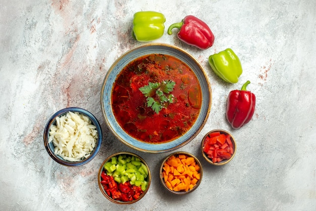 Vue de dessus délicieuse soupe de betterave ukrainienne célèbre bortsch avec de la viande et du poivre sur un espace blanc