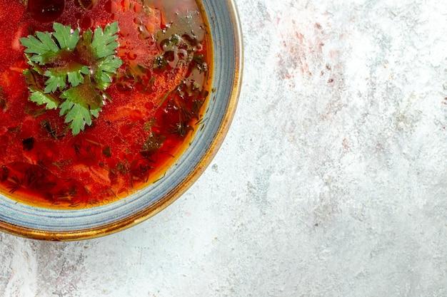 Vue de dessus délicieuse soupe de betterave ukrainienne célèbre de bortsch avec de la viande à l'intérieur de la plaque sur un espace blanc clair