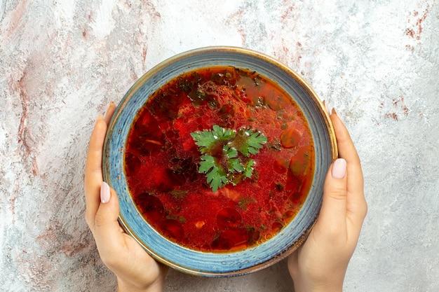 Vue de dessus délicieuse soupe de betterave ukrainienne célèbre de bortsch avec de la viande à l'intérieur de la plaque sur un espace blanc