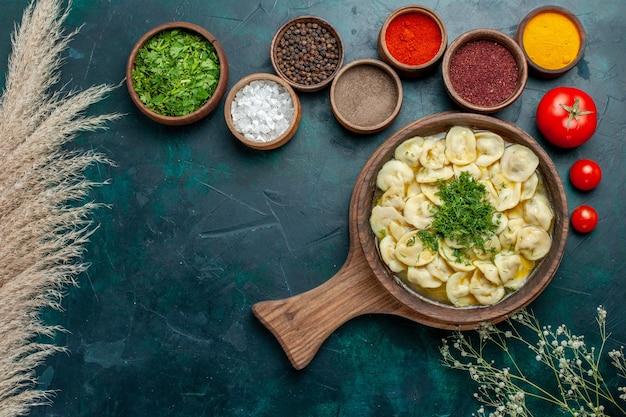 Vue de dessus délicieuse soupe de boulettes avec différents assaisonnements sur la soupe de pâte de légumes de viande de nourriture de surface verte