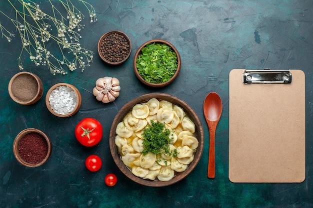 Vue de dessus délicieuse soupe de boulettes avec différents assaisonnements sur la surface verte soupe nourriture viande pâte légume