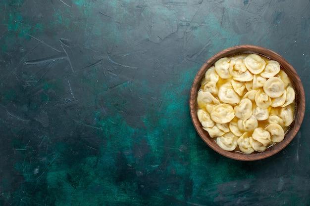 Vue de dessus délicieuse soupe de boulettes à l'intérieur de la plaque brune sur fond vert foncé pâte alimentaire soupe aux légumes viande