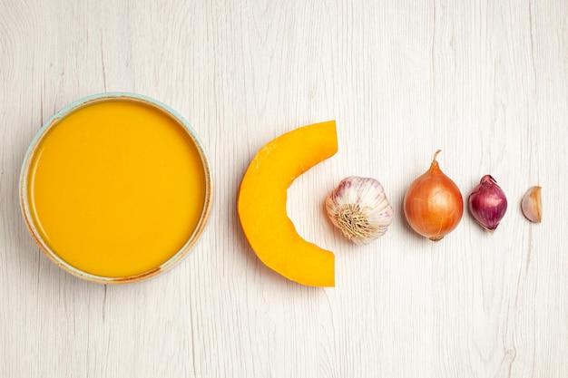 Vue de dessus une délicieuse soupe à la crème avec des légumes sur un bureau blanc soupe sauce repas crème dîner plat