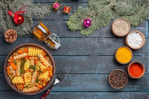 Vue de dessus délicieuse soupe de pâtes à partir de pâtes italiennes en spirale avec assaisonnements sur le bureau bleu foncé cuisine soupe de pâtes dîner plat de couleur