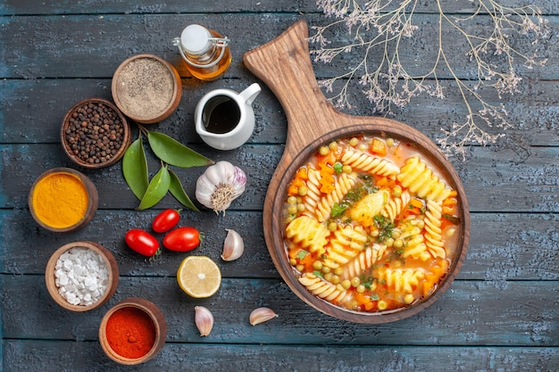 Vue de dessus délicieuse soupe de pâtes à partir de pâtes italiennes en spirale avec assaisonnements sur un bureau bleu foncé cuisine soupe de pâtes plat de couleur dîner