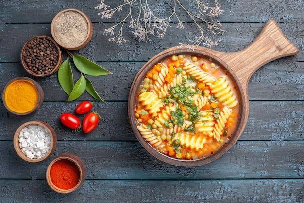 Vue de dessus délicieuse soupe de pâtes à partir de pâtes italiennes en spirale avec assaisonnements sur un bureau bleu foncé soupe de pâtes plat de couleur dîner cuisine