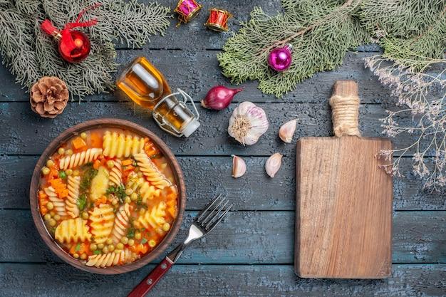 Vue de dessus délicieuse soupe de pâtes à partir de pâtes italiennes en spirale avec des verts sur le bureau bleu foncé cuisine soupe de pâtes dîner plat de couleur